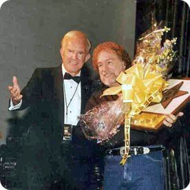 Ralph Emery with Gene Watson as he proudly displays his 'Golden Voice Award' trophy in Nashville on Monday 12 June 2000